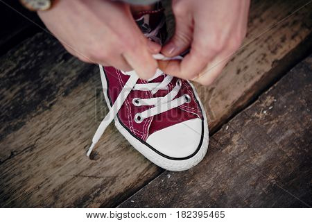 Close-up of woman hands tying shoelaces on wooden floor. Concept of jogging and hiking on nature.