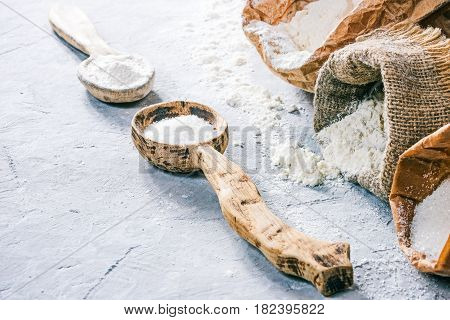 Packs of flour and sugar and rustic wood spoons of flour and sugar on the concrete background. Close up