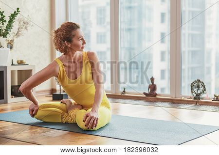 Sensual young woman is doing yoga at home. She is bending her arm while sitting in lotus position. Lady is looking out the window with serenity