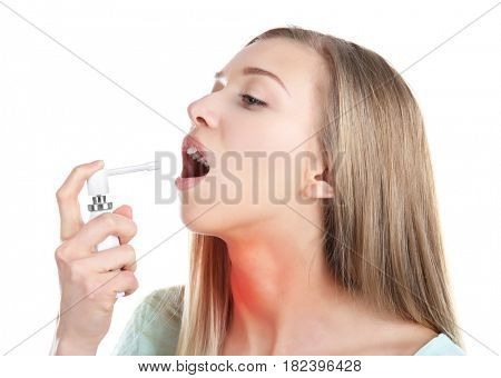 Allergies and sore throat concept. Sick young woman using spray on white background