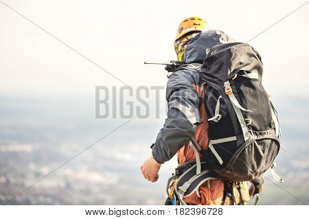 Close-up of a climber in gear and with a backpack with equipment on the belt, stands on a rock, at high altitude