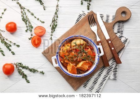 Bowl with delicious chicken cacciatore on wooden board