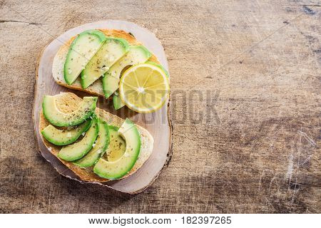 Avocado slices on the toasted bread with a piece of lemon. Top view.