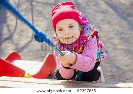 Little girl climbs the rope in the playground
