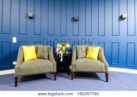 Old seat room with a blue wall a bouquet of flowers