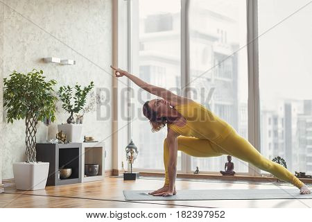 Fit calm young woman is practicing yoga at home. She is kneeling and stretching leg sideways. Her arm is raised up