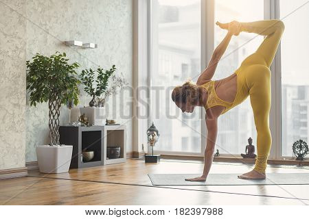 Slim young girl is standing on one leg and arm. She is stretching another foot up with efforts