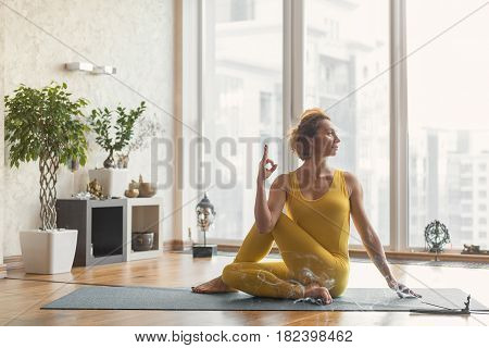 Serine girl is sitting in meditation position on mat and joining fingers. She is looking aside with relaxation. Incense stick is burning and spreading smoke around the room