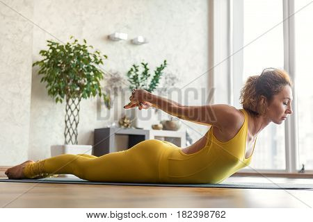 Slim serine young woman is stretching her athletic body while lying on mat. She is pulling her hands behind back. Her eyes are closed