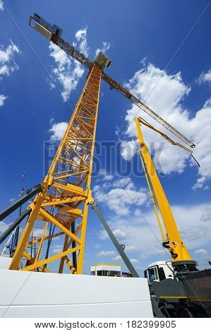 Construction crane and concrete pump on truck, heavy industry, blue sky and white clouds on background, bottom view