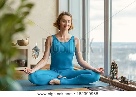 Happy young girl is sitting in lotus position and meditating. She is looking at camera and smiling. Portrait