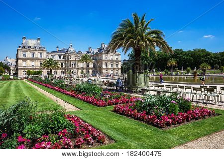 Paris France - Jule 07 2016: People enjoy sunny day in the Luxembourg Gardens in Paris. Luxembourg Palace is the official residence of the French Senate.