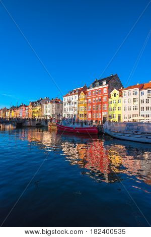 COPENHAGEN DENMARK - MARCH 11 2017: Tourists in Copenhagen Nyhavn district. Many of those houses lining the quays of Nyhavn have been the homes of prominent artists.