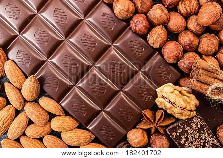 Chocolate Pieces, Filbert, Chocolate Shavings And Walnuts On Dark Background