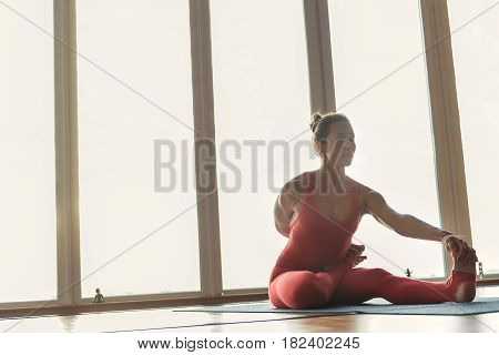 Portrait of relaxed young girl is flexing her body while sitting on mat in gym. She is stretching arm to leg while bending others. Her eyes are closed. Copy space in left side