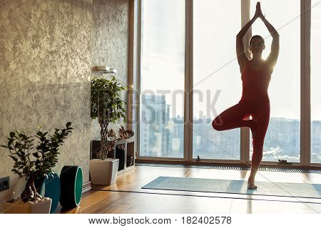 Wonderful combination of sport and relaxation. Full length portrait of calm young woman standing on one leg and meditating. She is raising arms and joining palms together. Sunshine from window
