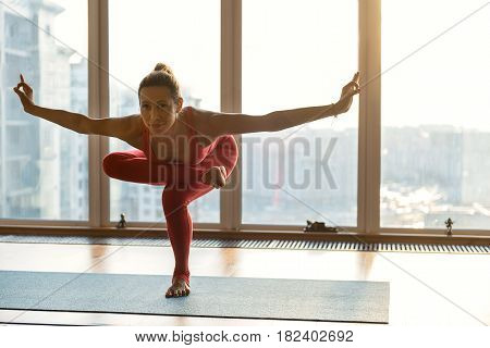 Sensual young woman is standing in yoga position and smiling. She is stretching arms sideways and looking forward with happiness