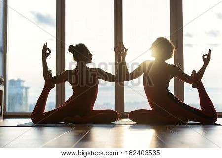 Professional two female athletes are sitting in yoga position together. They are touching their arms and looking at each other with serenity. Sunshine from big window