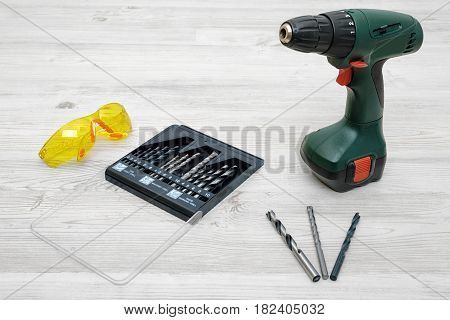 A cordless drill set to stand on a wooden table background with a set of bits in the box and yellow protective glasses around. Manual labor. Home improvement. Handyman tools.