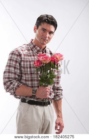 The darling man is holding a bunch of roses.
