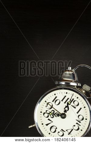 Retro metal alarm clock on a black wooden background. Open your eyes. Reveille to wake up. Place for text