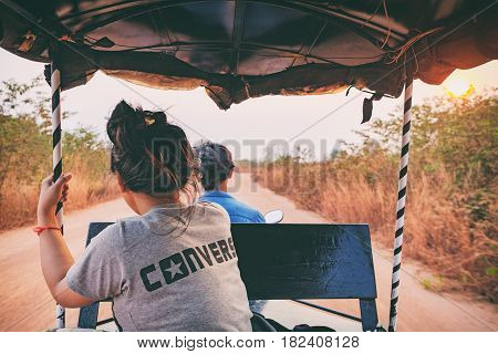 Siem Reap, Cambodia - February 5, 2016: Point of view shot from inside a moving tuk tuk. The passenger ahead looking forward to the road. Fast driving on rural sandy road among the fields at sunset