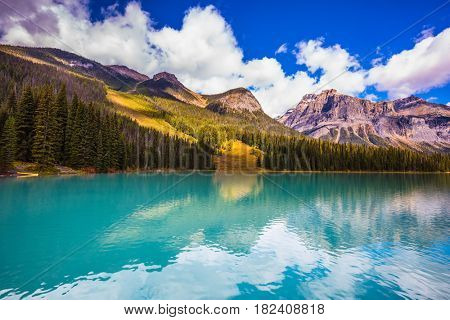 The smooth turquoise water in the wooded mountains. The concept of eco-tourism. The mountain Emerald lake. Yoho National Park, Canada. Sunny day in autumn
