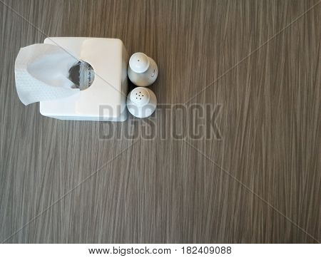 Tissue box with condiment bottle on wooden table,background concept,Copy space,Top view.