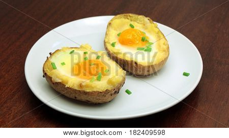 Twice baked potatoes with egg on top on white plate
