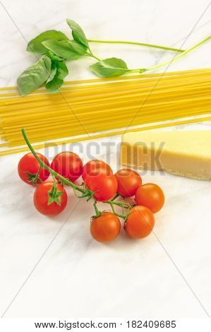 A photo of basic pasta ingredients on a white marble table. Fresh cherry tomatoes, a slice of cheese, spaghetti, basil leaves, and a place for text