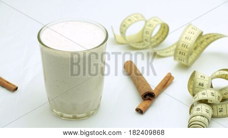 Waight loss smoothie with cinnamon in a glass on white background