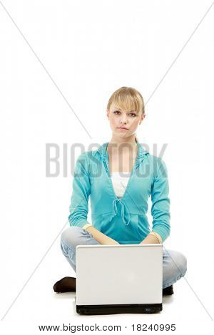 A young college girl sitting on the floor in front of her laptop