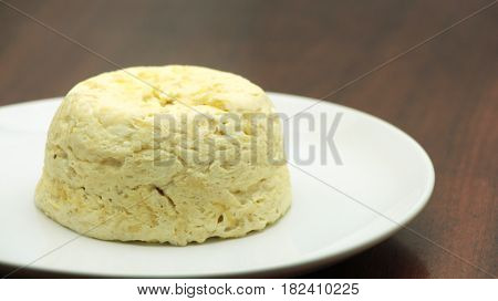 French baked cheese souffle on white plate close-up on the wooden table. horizontal