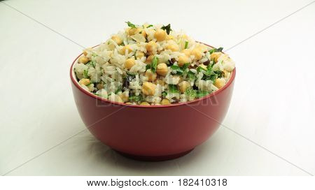 Middle Eastern Rice and Chickpeas Salad in Red Bowl on White Background