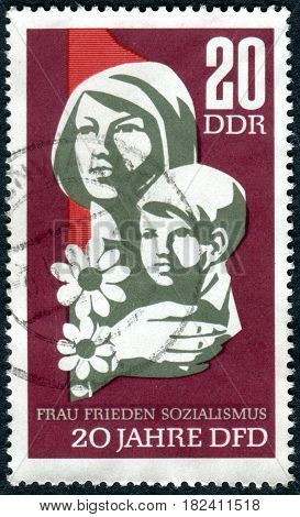 GERMANY - CIRCA 1967: A stamp printed in Germany (GDR) dedicated to 20th Anniversary of Democratic Women's Federation of Germany shows the woman with child circa 1967