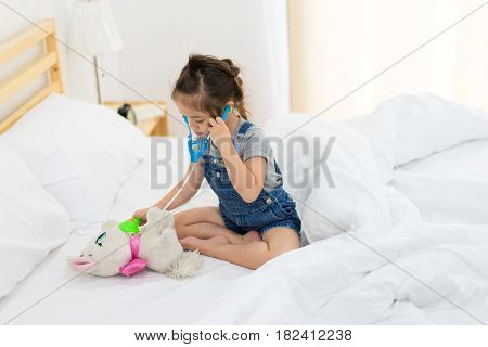 Little girl play a toy scope and doctor with a doll on the bed kid concept children and healthcare Learning concept