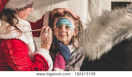 Little Girl Is Applying Makeup In A Stand