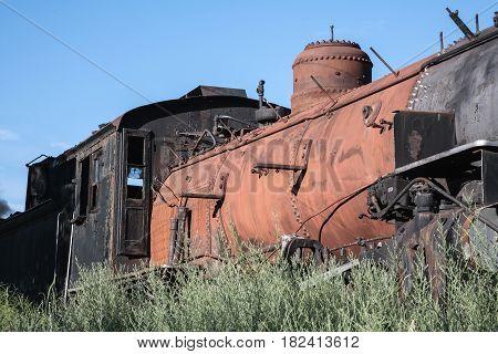 A vintage steam locomotive rusting away in a rail yard.
