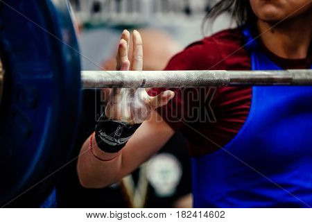 female powerlifter in hand wristbands competition bench press