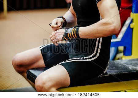 male powerlifter sitting in hand wristbands competition bench press