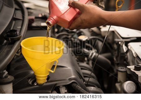 Close up man hands. Mechanic pouring new engine oil to car engine.