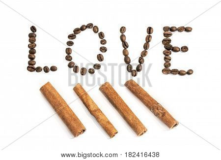 The word love written with coffee beans and cinnamon stick on white background