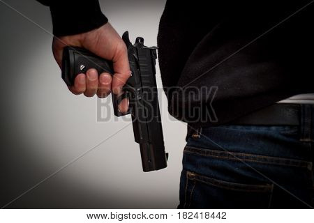 Killer Holding A Gun To His Feet, White Background In Front Of Him, Robbery, Murder, Crime