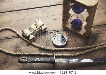 hourglass telescope compass and ropeon wooden table