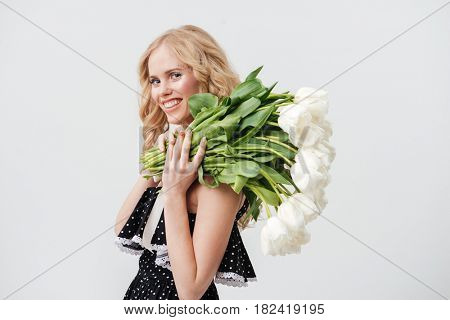Smiling blonde woman in dress posing sideways with  bouquet of flowers and looking at the camera over gray background