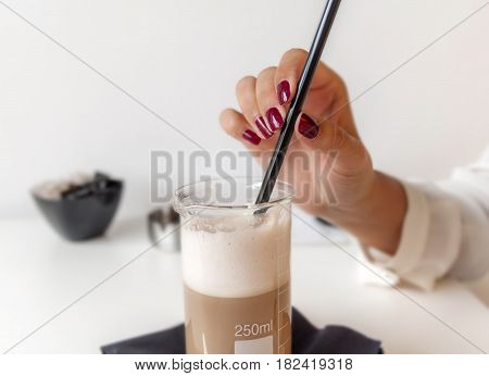 Woman holding straw with fresh latte in coffee shop on table