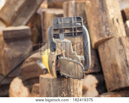 Electric saw chain on the background of sawn timber. The concept of processing wood to produce fuel.