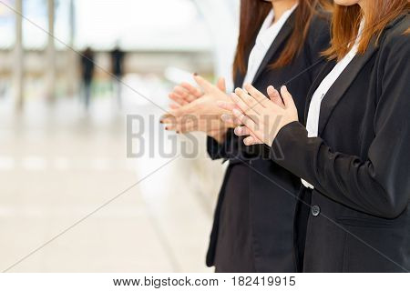 Two businesswoman clapping hands while standing for congratulation concept