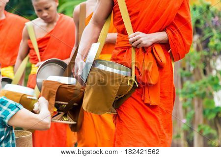 Luang Prabang, Laos - Mar 07 2015: Buddhist Alms Giving Ceremony In The Morning. The Tradition Of Gi