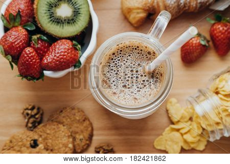 Hot Coffee And Sweet Breakfast: Croissant, Strawberry, Kiwi, Cereal, Milk. Top View